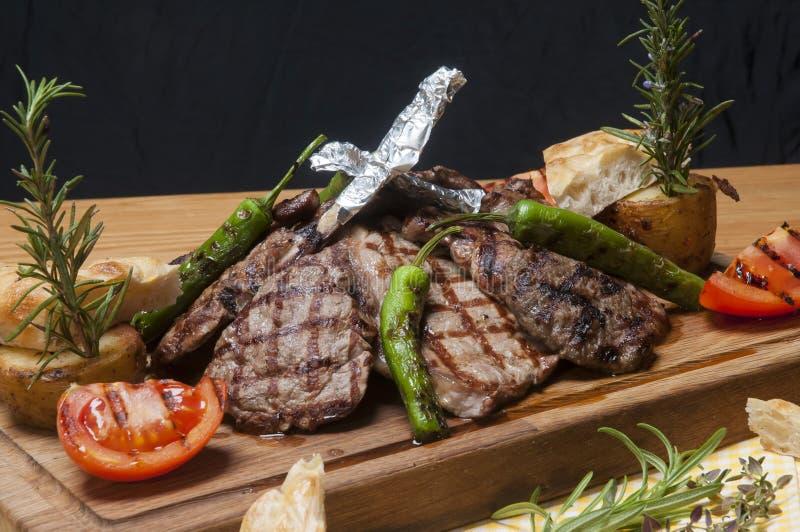 Mieszany mięsny grill na drewnianym półmisku z warzywami zdjęcie stock