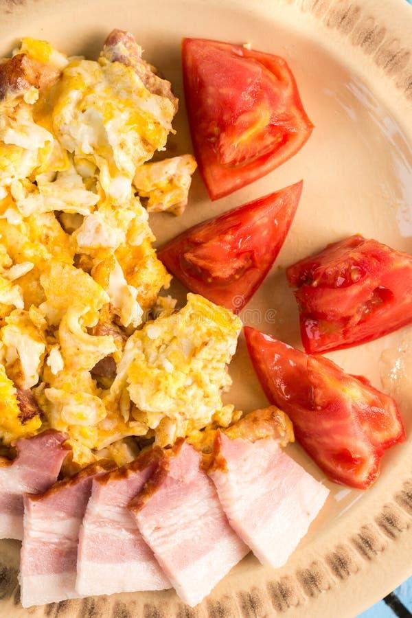 Mieszkań nieatutowi smażący jajka śniadaniowi z domową surową bekonu i pomidoru sałatką zdjęcie stock