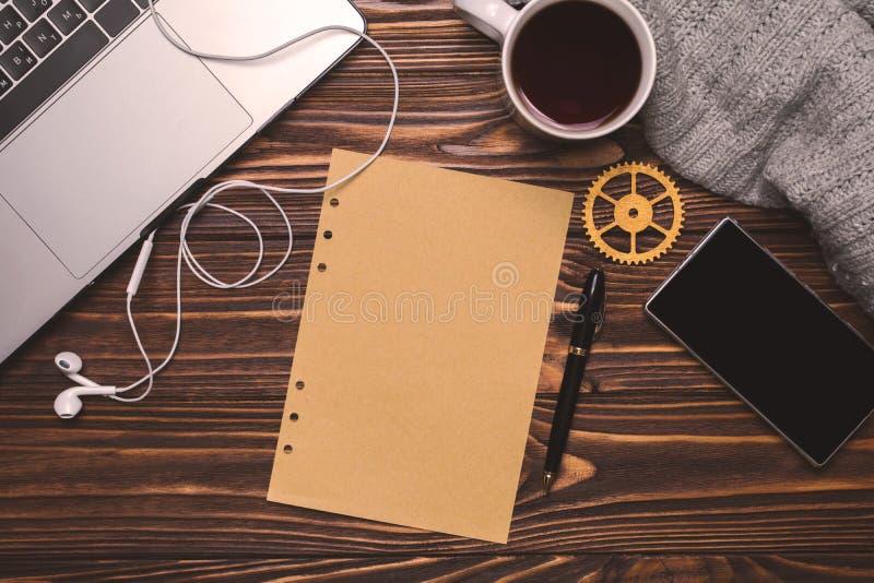 Mieszkania nieatutowy biurowy miejsce pracy Laptop, filiżanka, hełmofony, telefon, przekładnia, pióro, papier obraz royalty free