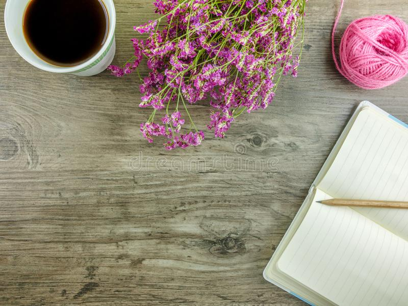 Mieszkania nieatutowy popielaty drewniany biurko z materiały, kwiatami i kawą, zdjęcie royalty free