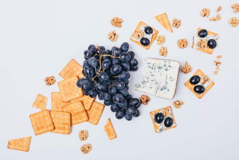 Mieszkania nieatutowy przygotowania canape i składniki: ser, winogrona, krakersy i orzechy włoscy, Odgórnego widoku przekąski kar fotografia stock