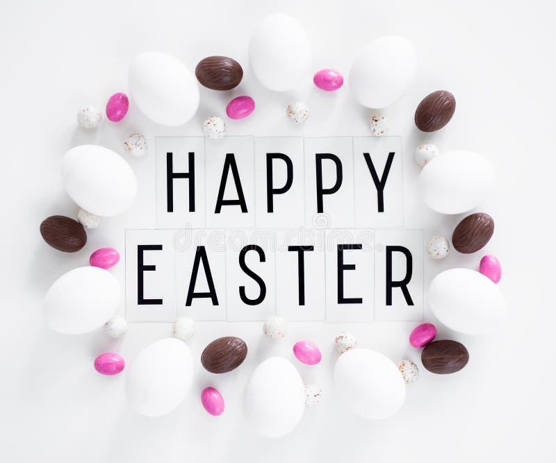 Mieszkania nieatutowy zakończenie w górę szczęśliwego Wielkanocnego teksta, jajek i cukierków nad bielem, fotografia stock