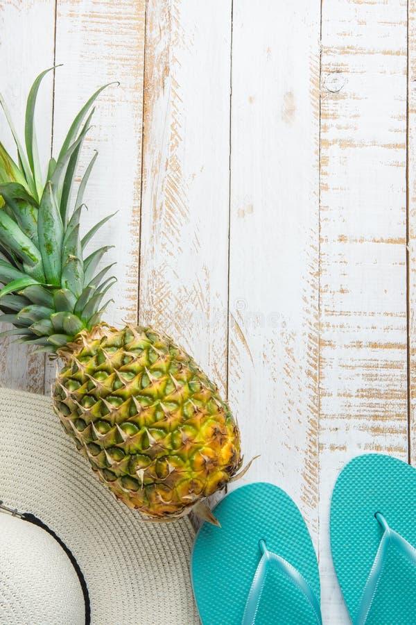 Mieszkania przygotowania Nieatutowy skład z Tropikalnych owoc Ananasowych kobiet Kapeluszowymi Błękitnymi kapciami na Białym Wykl zdjęcia stock