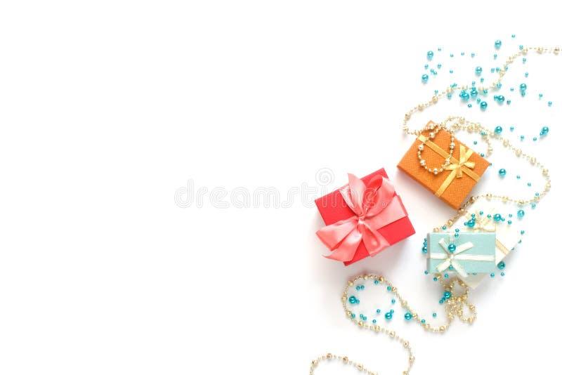 Mieszkanie świąteczne Prezenty świąteczne, błyszczące, błyszczące koraliki na białym tle Płaska warstwa, widok u góry, odstęp mię zdjęcie royalty free