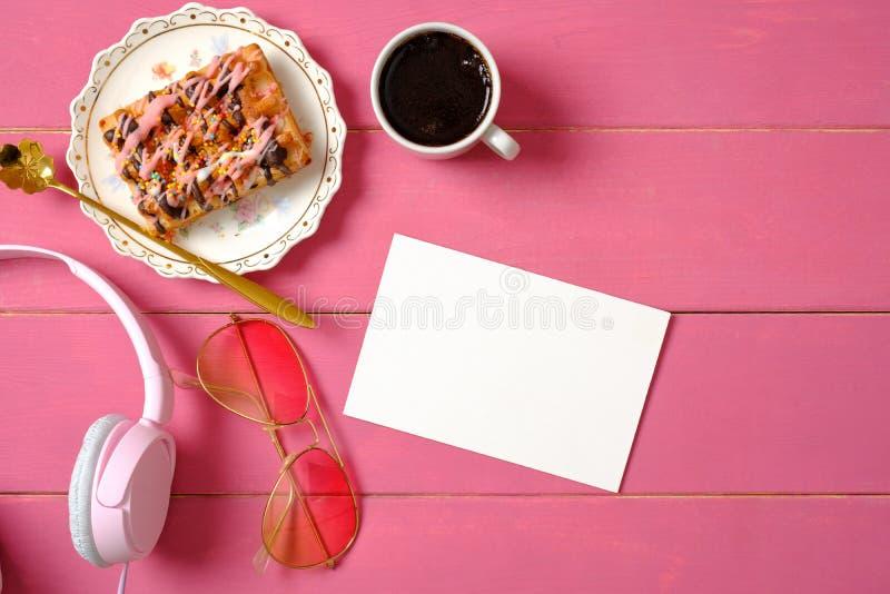 Mieszkanie dziewczyny nieatutowi akcesoria na r??owym drewnianym tle Pusta papierowa karta, he?mofony, smakowity tort, szk?a Odg? obrazy stock