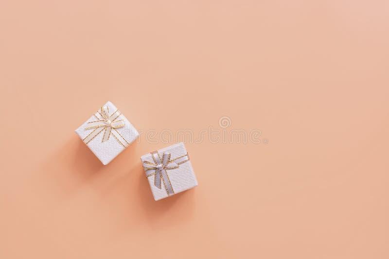 Mieszkanie kłaść dwa wakacyjnego prezenta pudełka szary i biały na pastelowych menchii tle Odg?rny widok, kopii przestrze? fotografia royalty free