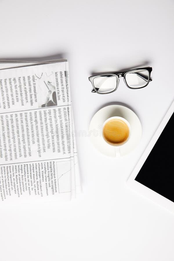 mieszkanie kłaść z eyeglasses kawa, cyfrowa pastylka i gazety, na bielu zdjęcia stock