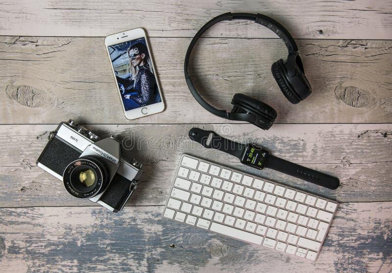 Mieszkanie Kłaść z starą SLR filmu kamerą, iPhone, Jabłczanym zegarkiem, klawiaturą i hełmofonami, fotografia royalty free