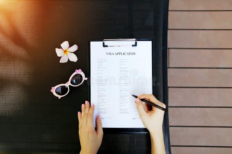 Mieszkanie kobiety nieatutowe ręki, pióro wniosek wizowy dla podróży i okulary przeciwsłoneczni, kwitną Przód używać z Otwartym c zdjęcia royalty free