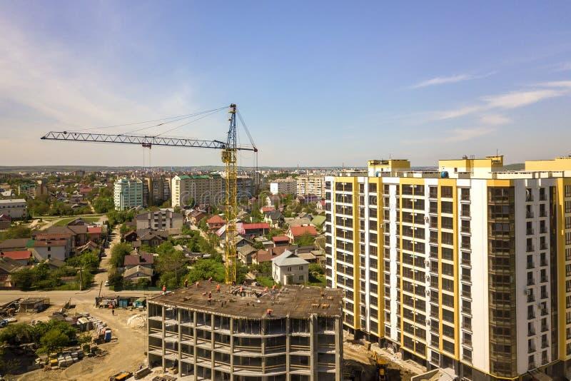 Mieszkanie lub biurowy wysoki budynek w budowie Pracujący budowniczowie i basztowi żurawie na jaskrawej niebieskie niebo kopii in obrazy royalty free