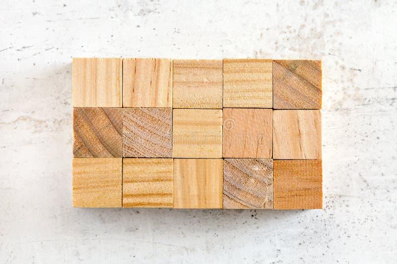 Mieszkanie nieatutowa fotografia, piętnaście drewnianych sześcianów układających w 3, 5 siatce na białej działanie desce x, Dodaj obraz stock