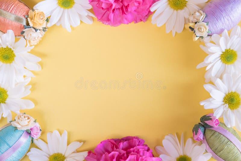 Mieszkanie nieatutowa rama Wielkanocni jajka i kwiaty na stałym pastelowym żółtym tle zdjęcie royalty free