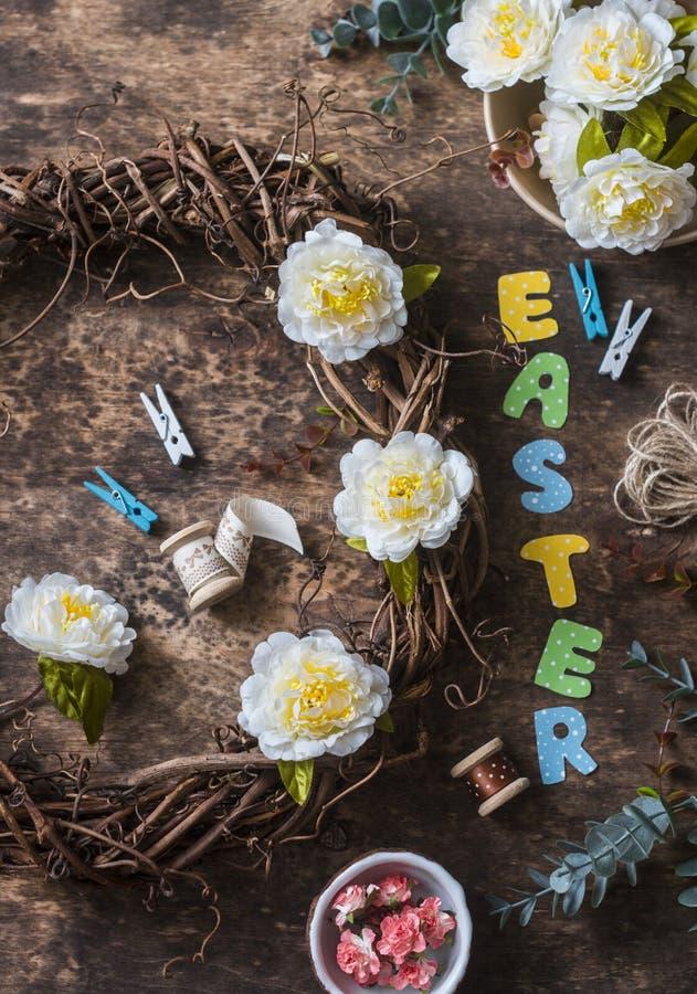 Mieszkanie nieatutowe handmade Wielkanocne dekoracje - wianek winogrady z kwiatami, papierowi króliki, faborki na drewnianym tle, zdjęcia royalty free