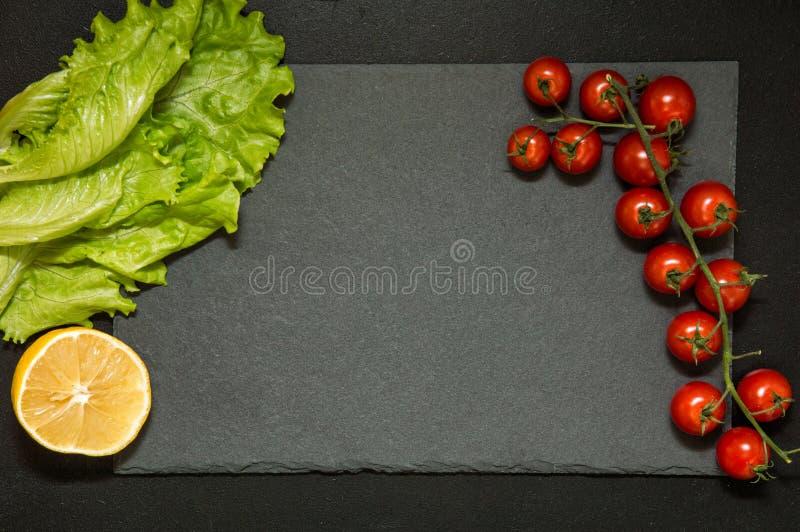 Mieszkanie nieatutowy Czarna tnąca deska otaczająca świeżymi warzywami kosmos kopii obraz royalty free
