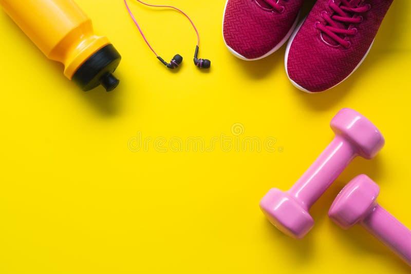 Mieszkanie nieatutowy czerwoni sportów buty, różowi dumbbells, słuchawki, butelka o zdjęcie stock