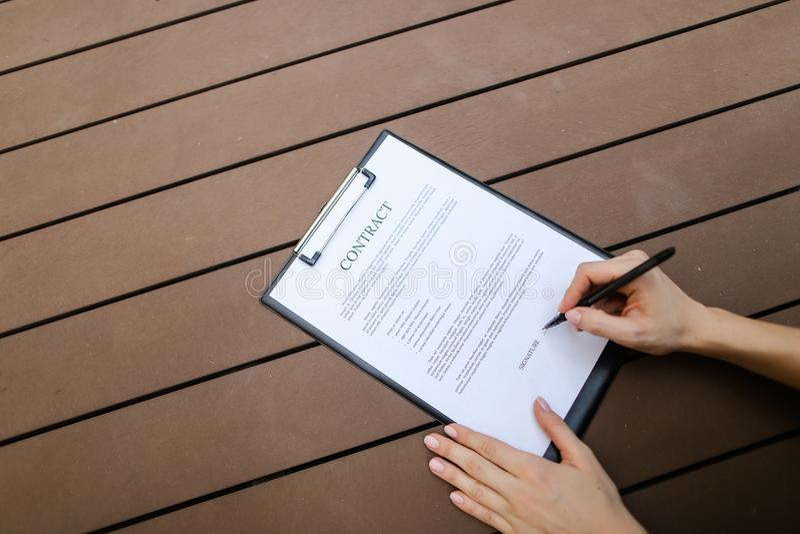 Mieszkanie nieatutowy kobiet ręki podpisuje kontraktacyjnego, drewnianego backgroung, przód fotografia royalty free