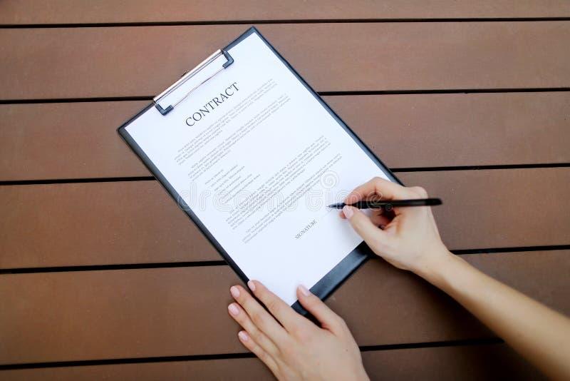 Mieszkanie nieatutowy kobiet ręki podpisuje kontraktacyjnego, drewnianego backgroung, Przód używać z Otwartym chrzcielnica licenc zdjęcie royalty free