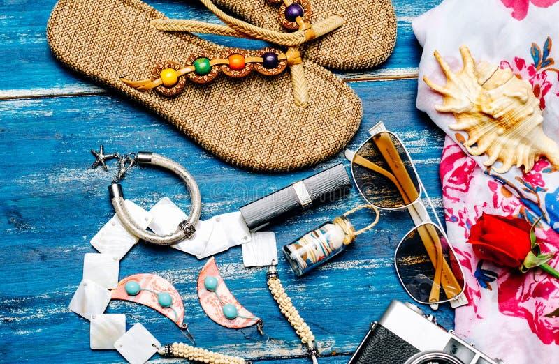 Mieszkanie nieatutowy lato moda z kamera kapci okularami przeciwsłonecznymi i innymi dziewczyn akcesoriami na błękitnym tle zdjęcia stock