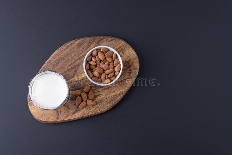 Mieszkanie nieatutowy minimalizm migdału mleko w szkle z garść migdał dokrętkami na drewnianym stojaku z kopią przestrzeń fotografia stock
