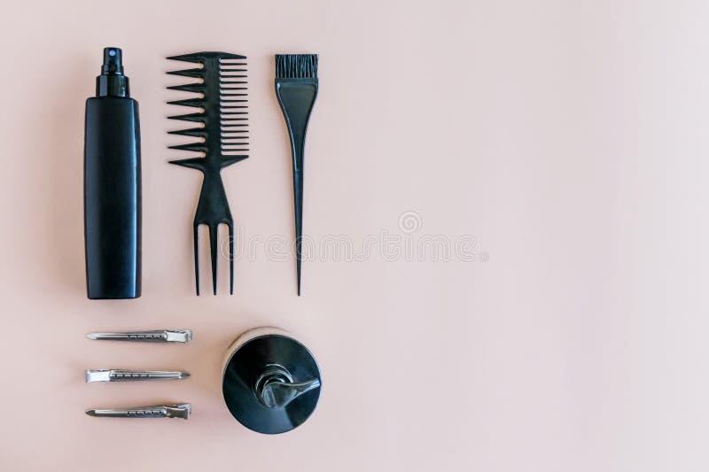 Mieszkanie nieatutowy Minimalny skład z czarni włosy salonu narzędziami na pastelowym tle zdjęcia stock