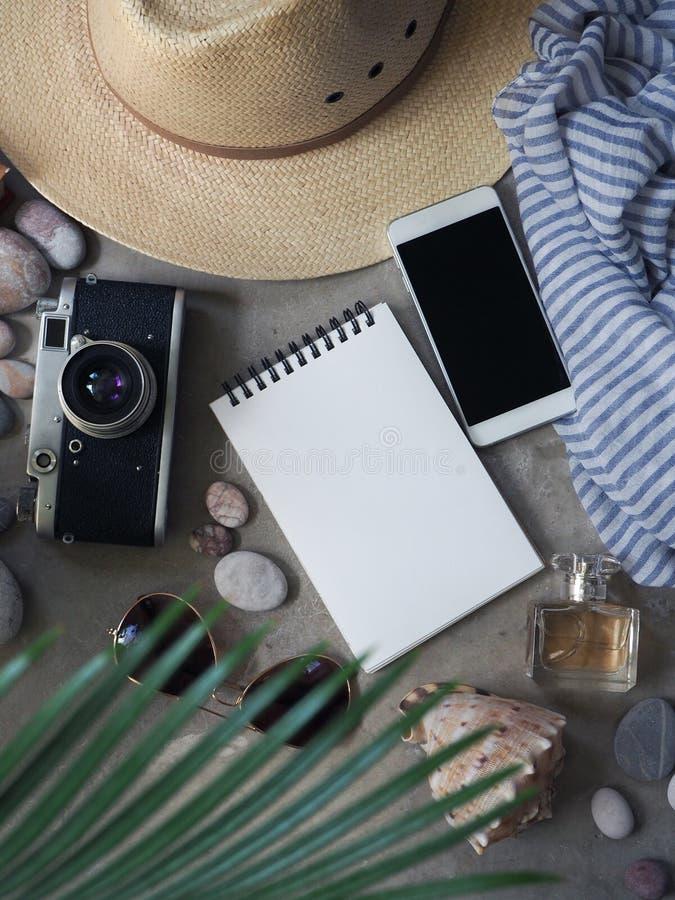 Mieszkanie nieatutowy, odgórnego widoku podróżnika ` s notatnik, kapeluszowi okulary przeciwsłoneczni, kamera, pachnidło zdjęcia stock