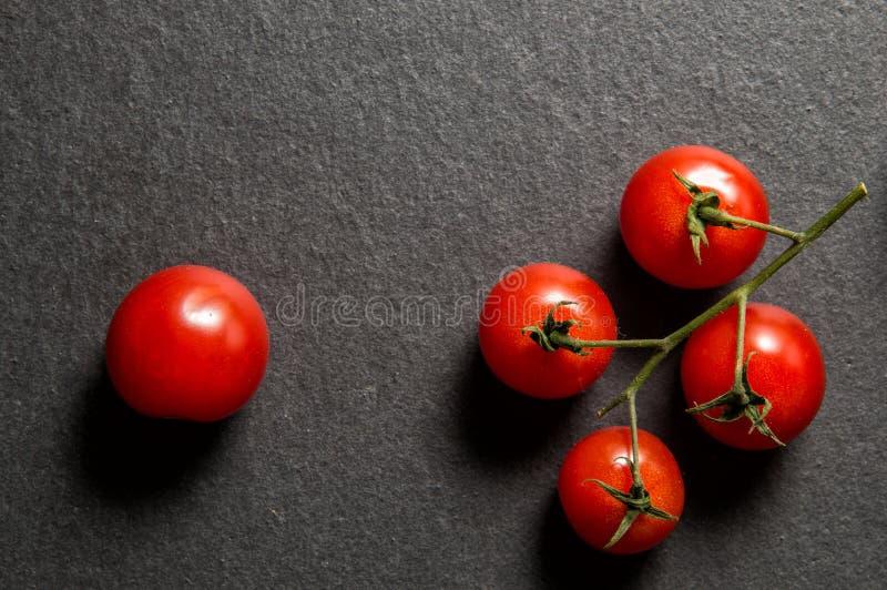 Mieszkanie nieatutowy, odgórny widok z bliska Mały sprig jaskrawi soczyści czereśniowi pomidory W pobliżu jest jeden pomidor Czar obrazy stock