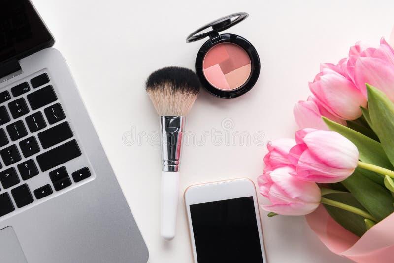 Mieszkanie nieatutowy otwarty laptop, smartphone z pustym ekranem, kwiaty i makeup, szczotkujemy obrazy stock