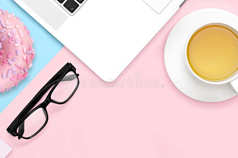 Mieszkanie nieatutowy projekt pracy biurko z laptopu notatnikiem, herbacianym kubkiem, oczu szkłami na pastelowych menchiach i bł obraz royalty free