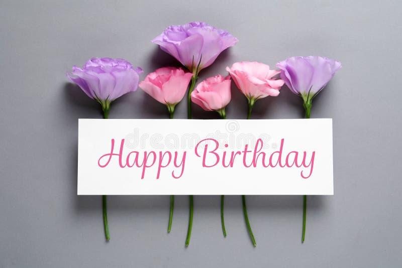 Mieszkanie nieatutowy skład Eustoma kwiaty i karta z powitania wszystkiego najlepszego z okazji urodzin fotografia stock