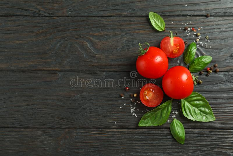 Mieszkanie nieatutowy skład z świeżymi pomidorami, solą, pieprzem i basilem na drewnianym tle, przestrzeń dla teksta fotografia royalty free