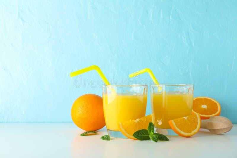Mieszkanie nieatutowy skład z świeżymi sokami pomarańczowymi, drewnianym juicer, mennicą, pomarańczami i drewnianym juicer na bie obrazy royalty free