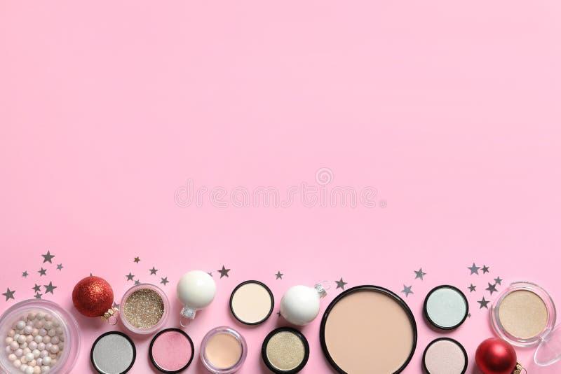 Mieszkanie nieatutowy skład z makeup produktami i Bożenarodzeniowym wystrojem na koloru tle obraz stock