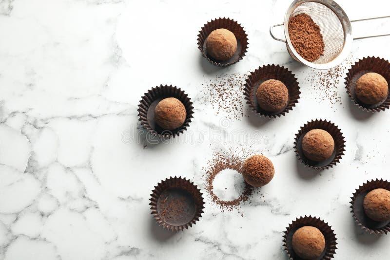 Mieszkanie nieatutowy skład z smakowitymi surowymi czekoladowymi truflami na marmurowym tle zdjęcie stock