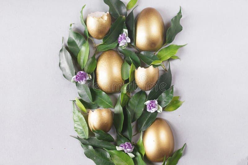 Mieszkanie nieatutowy sk?ad z z?ocistymi jajkami 2 forsuj? piskl?ca poj?cia Easter jajek kwiat?w trawa maluj?cych umieszczaj?cych zdjęcia stock