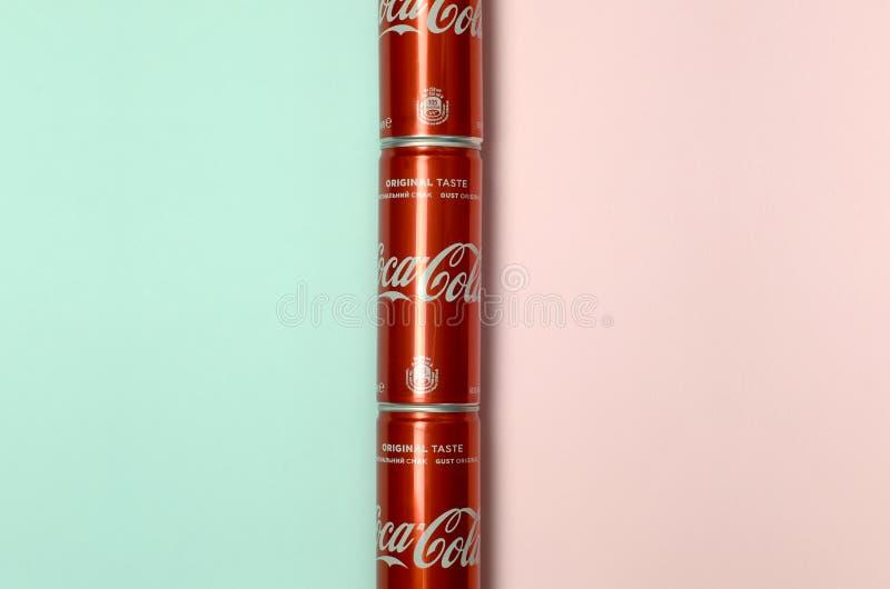 Mieszkanie nieatutowy strzał carbonated czerwonego napój blaszanych puszek koka-kola kłaść na pastelowym błękitnym i koralowym tl obrazy stock