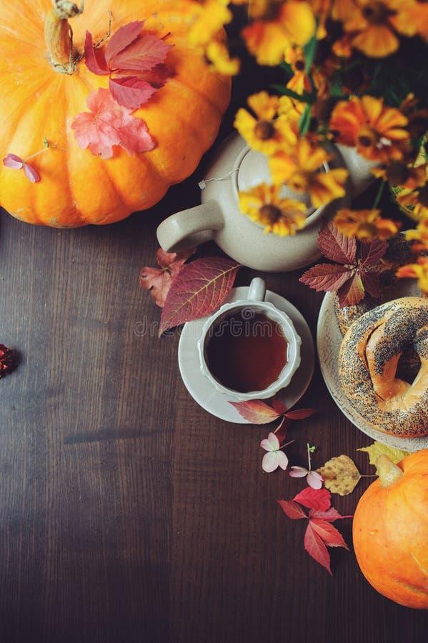 Mieszkanie nieatutowy wygodny jesieni śniadanie na stole w dom na wsi Gorąca herbata, banie, bagels i kwiaty, zdjęcie stock