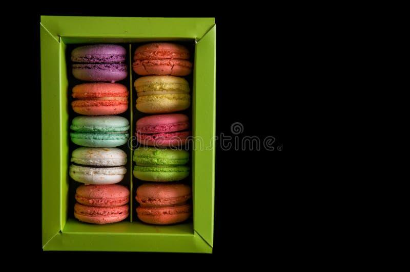 Mieszkanie nieatutowy z bliska Słodcy i kolorowi francuscy macarons ustawiający w jasnozielonym pudełku, odosobnionym na czarnym  zdjęcia royalty free