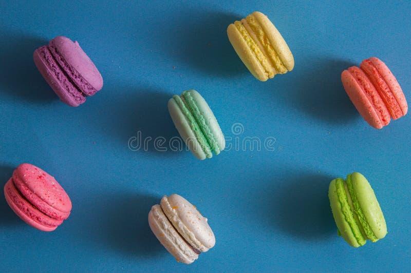 Mieszkanie nieatutowy z bliska Słodcy jaskrawi francuscy macarons barwią rozkładają na krawędzi niebieska tła zdjęcia royalty free