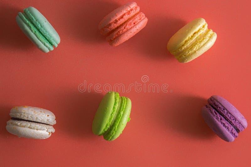 Mieszkanie nieatutowy z bliska Słodcy kolorowi francuscy macarons barwią rozkładają na krawędzi Tło koloru żywy koral 2019 zdjęcie royalty free