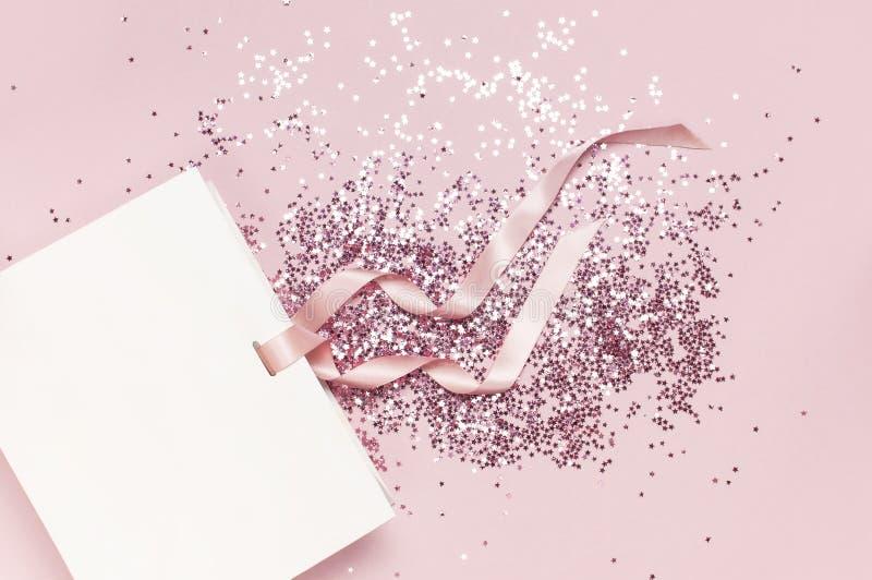 Mieszkanie odgórnego widoku prezenta nieatutowa Biała torba i holograficzni błyskotliwość confetti w postaci gwiazd na różowym tl obraz stock