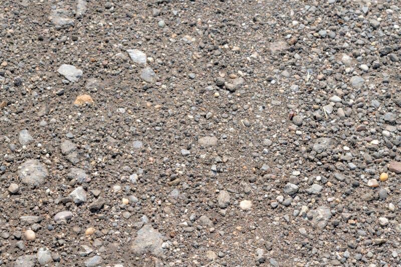 Mieszkanie staczająca się szara piaskowata ziemia z otoczakiem obraz stock