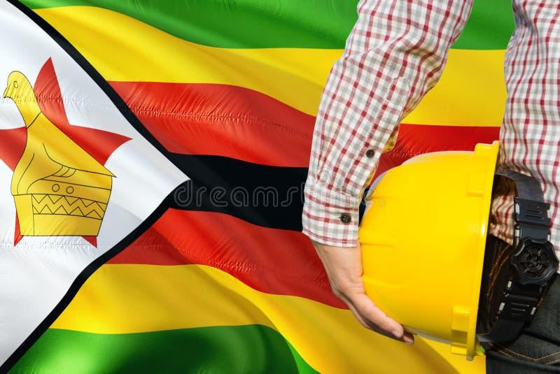 Mieszkaniec Zimbabwe inżynier trzyma żółtego zbawczego hełm z machać Zimbabwe chorągwianego tło Budowy i budynku poj?cie obraz stock