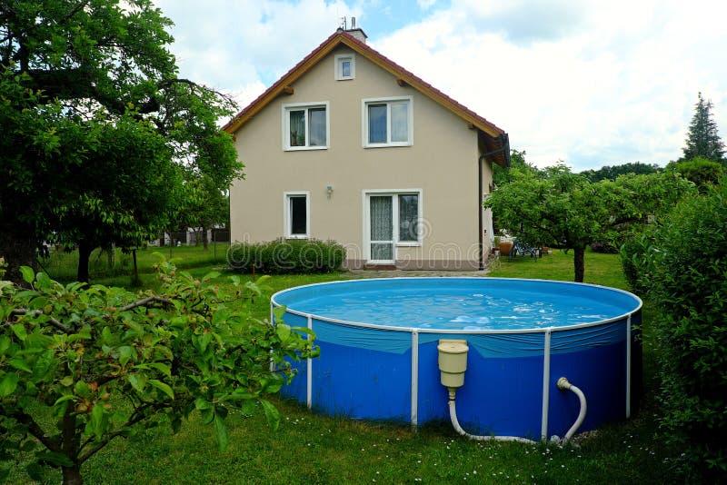 Mieszkaniowy dom w beżu z ogrodowym basenem zdjęcia royalty free