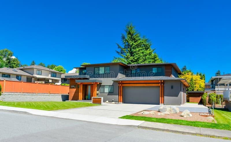Mieszkaniowy dom z szerokim garażu drzwi i betonu podjazdem obraz stock