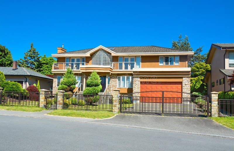Mieszkaniowy dom z szerokim garażem kształtujący teren, jard metalu ogrodzenie w przodzie, i zdjęcia stock