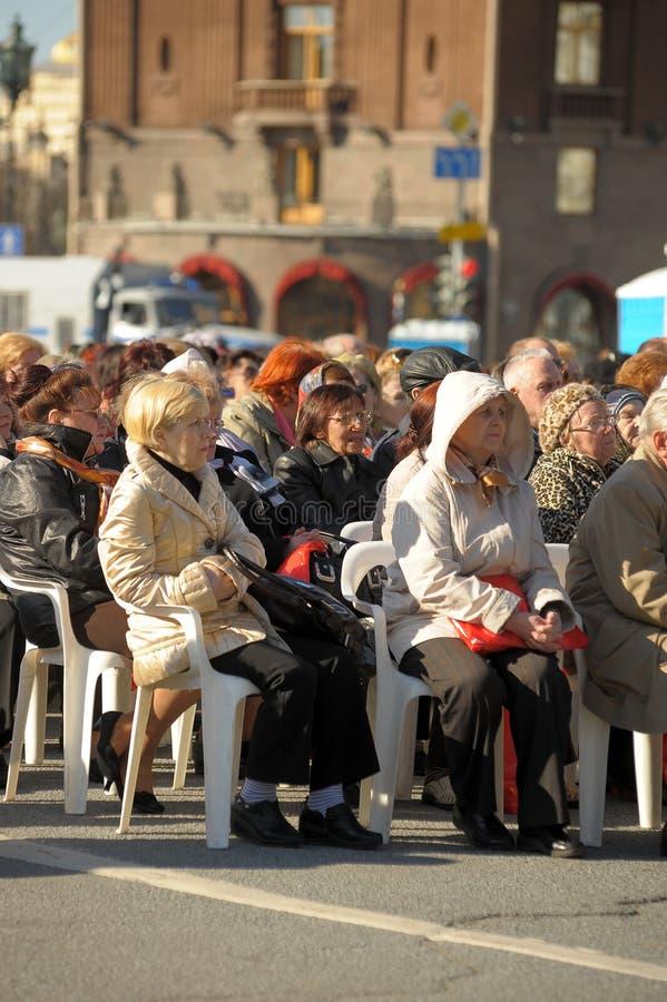 Mieszkanowie i weterani siedzą słuchanie koncert na cześć zwycięstwo dzień, Świąteczni wydarzenia w centrum miasta obraz royalty free