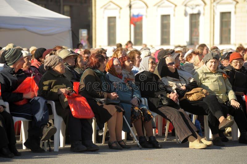 Mieszkanowie i weterani siedz? s?uchanie koncert na cze?? zwyci?stwo dzie?, ?wi?teczni wydarzenia w centrum miasta obraz royalty free