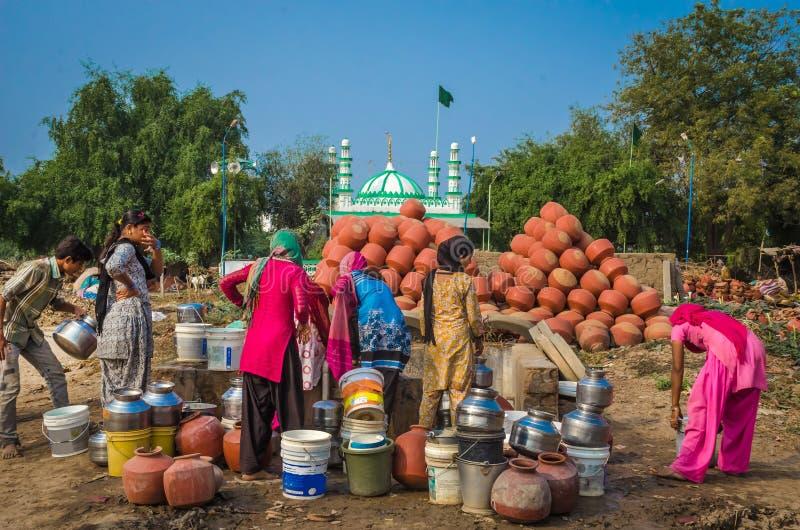 Mieszkanowie wioska Makarba zbierają wodę od dostawy wody niedalekiego well zdjęcie stock
