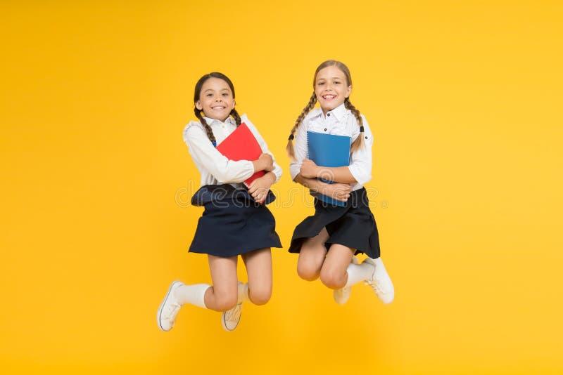 ?mieszna edukacja małe dziewczynki w mundurku szkolnym rozochoceni koledzy z klasy z workbook dzieciaki uczy się gramatykę Popier obraz royalty free