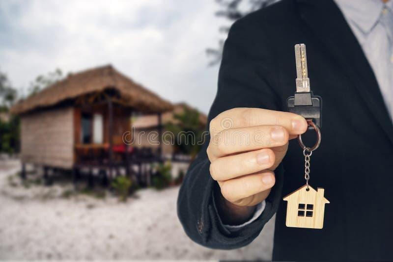 Mieten Sie einen Bungalow am Strand für einen Urlaub Mann kauft neues Haus Handaufnahmeschlüssel Schlüsselanhänger der nahen Hand stockbilder